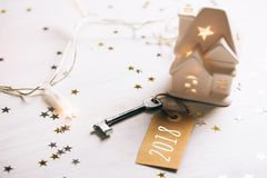 Key to 2018 year. Small toy white house with a roof, lights and key standing on wooden background with sparkles. New Year coming concept Stock Photo