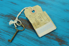 Key to your health. Key with a tag and the handwritten words 'your health' on it. Rustic blue wooden background Royalty Free Stock Photography