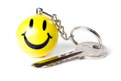 Key and trinket. Key with yellow smiling trinket isolated on white background Stock Images