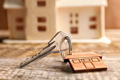 Key with trinket and blurred house model. On background Royalty Free Stock Images