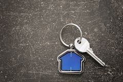 Key with trinket in shape of house. On dark table Stock Photo