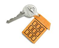 Key with trinket in shape of house. On white background Royalty Free Stock Photos