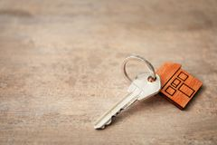Key with trinket in shape of house. On wooden table Stock Photography