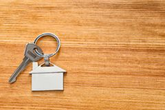 Key with trinket in shape of house. On wooden table Stock Images