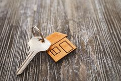 Key with trinket in shape of house. On wooden table Royalty Free Stock Photo