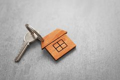 Key with trinket in shape of house. On wooden table Royalty Free Stock Image