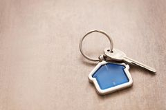 Key with trinket in shape of house. On wooden table Stock Photos