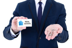 Key and visiting card in male real estate agent hand isolated on Stock Photography