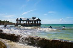 Key West Cityscape. Beautiful Key West shoreline with a pier and waves splashing over the seawall Royalty Free Stock Images