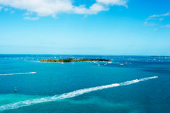 Key West Island. Isolated island off the coast of Key West surrounded by blue ocean waters and sport boats Stock Photo