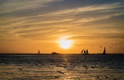 Key West Sunset in Mallory Square. Sunset over the water at Mallory Square in Key West, Florida. Orange sky with silhouettes of boats and birds Royalty Free Stock Photography