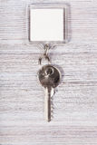 Key with white blank keychain on wood table Royalty Free Stock Images