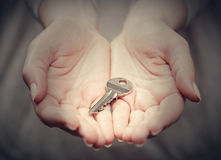 Key in woman's hand in gesture of giving. Concept of success in live, business solution, real estate etc Stock Photos