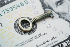 Key for world and United States economy, FED consider interest r. Ate hike, important bronze mini key on US Federal Reserve emblem on dollars banknote royalty free stock image