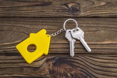 Key with yellow shaped house keychain on chain on wood texture background. Idea:. Buying a house, renting, selling real estate. Mortgage. Loan for housing Royalty Free Stock Photography