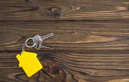 Key with yellow shaped house keychain on chain on wood texture background. Idea: buying a house, renting, selling real estate. Mortgage. Loan for housing stock photo