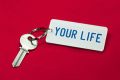 Key of your life. Key and key fob labelled your life on a red background stock photo