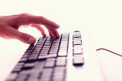 Keyboard. Hand typing on a white computer keyboard. White background Royalty Free Stock Photos
