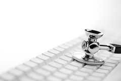 Keyboard ans stethoscope in B + W. Part of stethoscope resting on white keyboard with large empty area on left side for type royalty free stock photography
