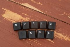 The keyboard buttons the inscription love music. Wooden background stock photography