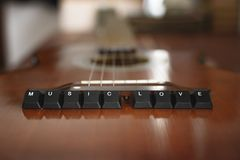 Keyboard buttons lettering music love on top of the Acoustic guitar. Wooden background stock photography