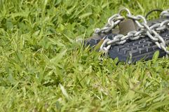 Keyboard chained on grass. Stock Photo