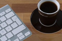 Keyboard and coffee cup. Grey wireless keyboard with white keys. Brown espresso mug. On wooden table top Royalty Free Stock Photo