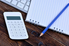 Keyboard computer with notepad and calculator on table Royalty Free Stock Image