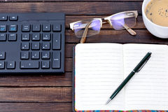 Keyboard computer with notepad and eyeglasses on table Royalty Free Stock Photo