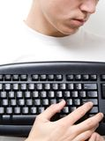 Keyboard Concept 5. High Key - Portrait of a young man holding computer keyboard in front of his chest stock photography