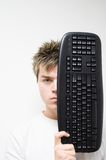 Keyboard Concept1. High Key - Portrait of a young man holding computer keyboard in front of his face royalty free stock photography