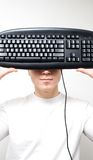 Keyboard Concept2. High Key - Portrait of a young man holding computer keyboard in front of his face Stock Photo
