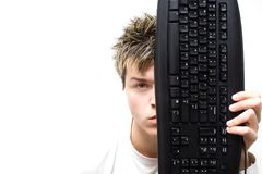 Keyboard Concept4. High Key - Portrait of a young man holding computer keyboard in front of his face stock image