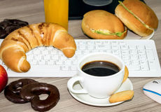 Keyboard covered with food that we eat during work Royalty Free Stock Photo