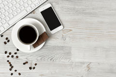 Keyboard, cup of hot coffee and smartphone on wooden surface with copy space Royalty Free Stock Photos