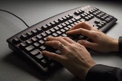 Keyboard with hands. Moody keyboard shot with woman's hands on gray bak ground stock photos