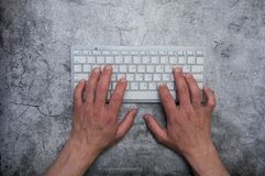 Keyboard with hands on a dark gray background. Asphalt concrete wallpaper. Context, writer, programmer, office work. Keyboard with hands on a dark gray stock photo