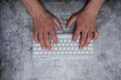 Keyboard with hands on a dark gray background. Asphalt concrete wallpaper. Context, writer, programmer, office work. Keyboard with hands on a dark gray stock image