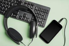 Keyboard headphones and smart telephone Royalty Free Stock Photos