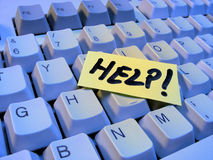 Keyboard help. Help word on a post-it, on a keyboard Royalty Free Stock Image