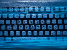 Keyboard with inscription Merry Christmas illuminated by blue light Royalty Free Stock Image