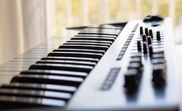 A keyboard instrument and its recording studio qualities. An electronic keyboard is set in a bright room. It has an 8 channel control board built in with faders stock photos