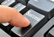 Keyboard with key to success. Finger pressing an enter key with the word success Stock Photos
