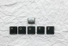 Keyboard keys laid out the word house. On a crumpled paper,as background royalty free stock photography
