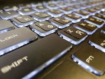 Keyboard of a laptop with illumination. Macro snapshot of a laptop keyboard. Russian and English letters. Bright nillumination buttons stock photos
