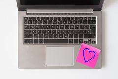 Laptop keyboard with heart note. Keyboard of a laptop with a red note written heart on white background Stock Images