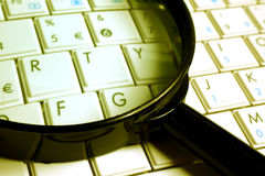 Keyboard with a magnifying glass Royalty Free Stock Photos