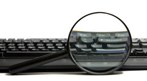 Keyboard with a magnifying glass Royalty Free Stock Image