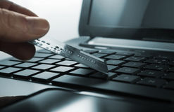 Keyboard. Mans hand with credit card and open black laptop keyboard royalty free stock photography
