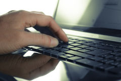 Keyboard. Mans hand on open black laptop keyboard royalty free stock images